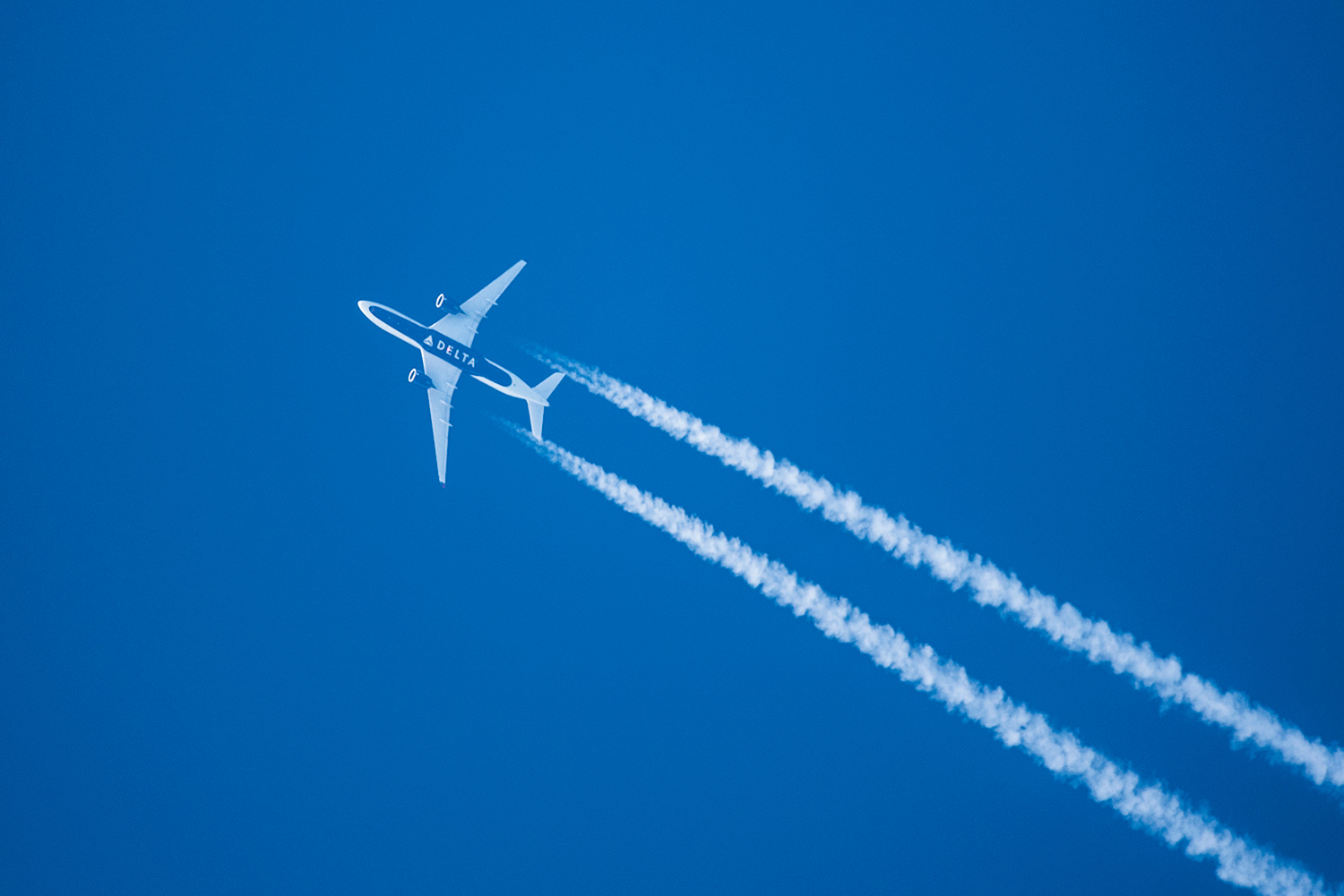 Airbus A350 jet with contrails cruising at 34,000 feet en route Tokyo to Seattle