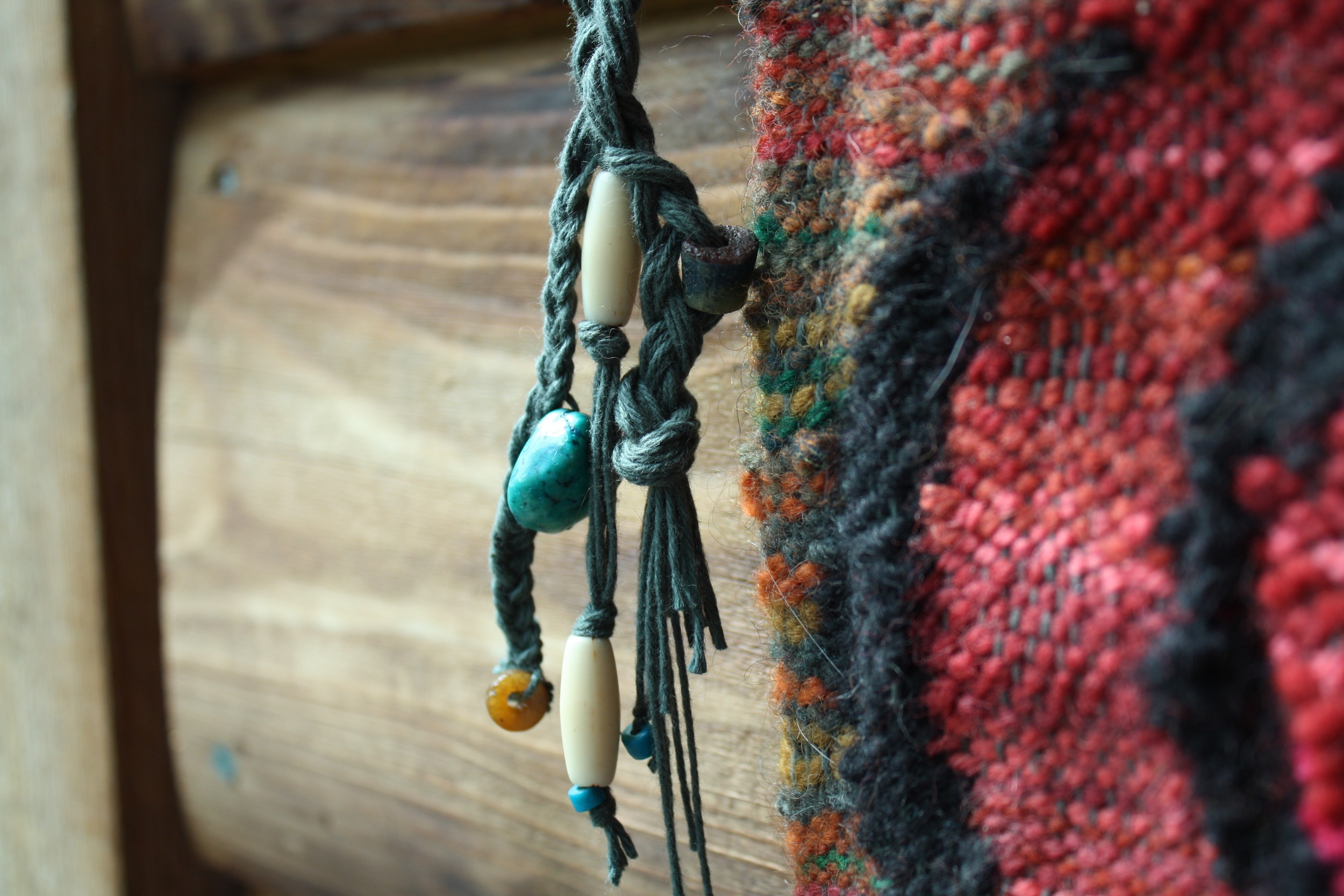 """Beads and bones are finishing touches on """"Wombsight"""" a tapestry handwoven by 14 Mile Farm"""