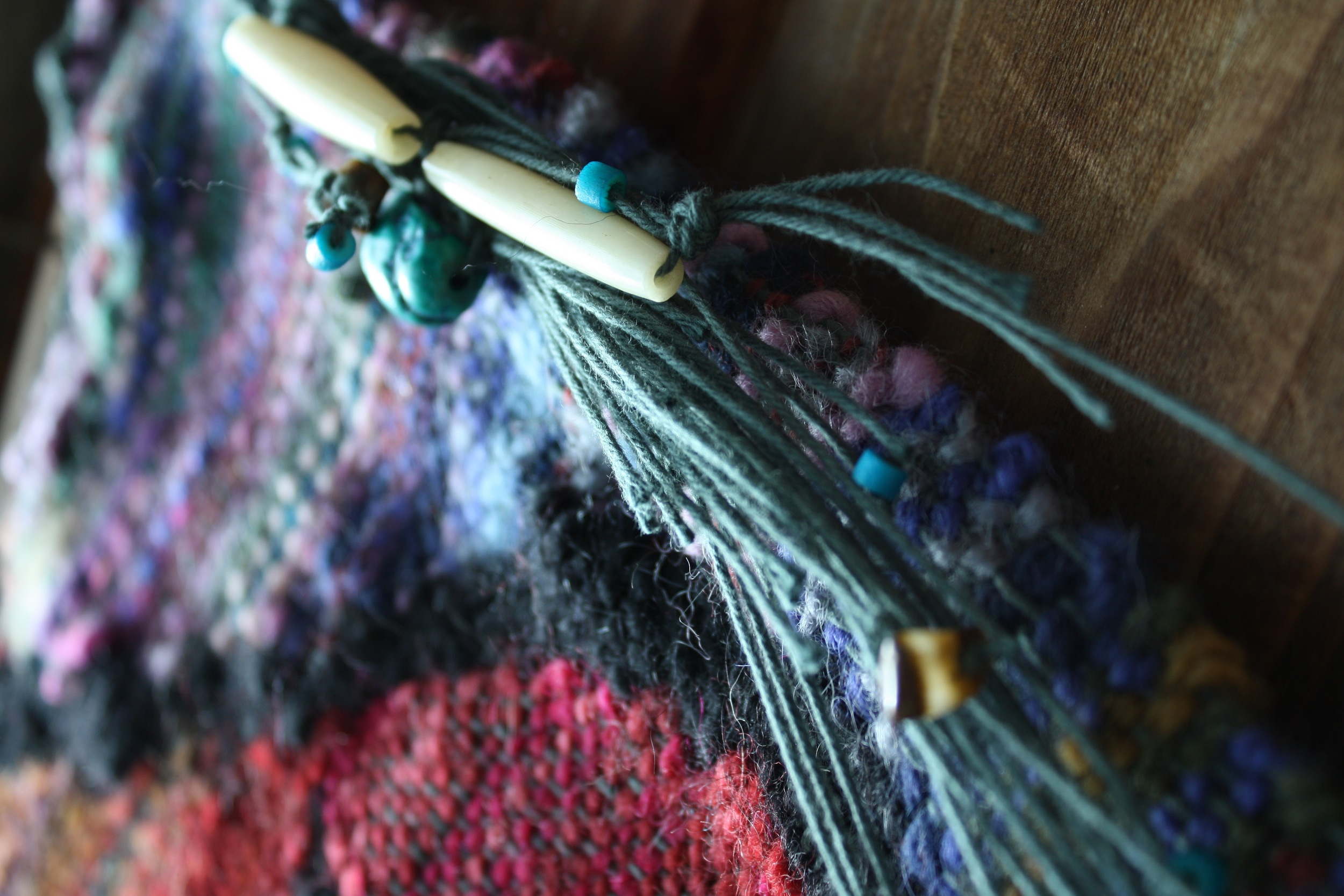"""Tiger's eye, turquoise, and bone on """"Wombsight"""" a tapestry handwoven by 14 Mile Farm"""