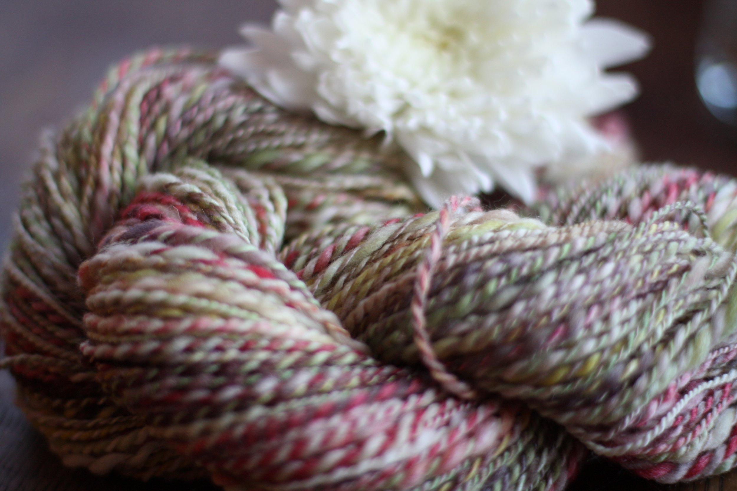 A skein of handspun wool/silk yarn in shades of cream, red, brown, and green rests on a weathered wooden table with a white flower | 14 Mile Farm Handweaving and Homesteading in Alaska