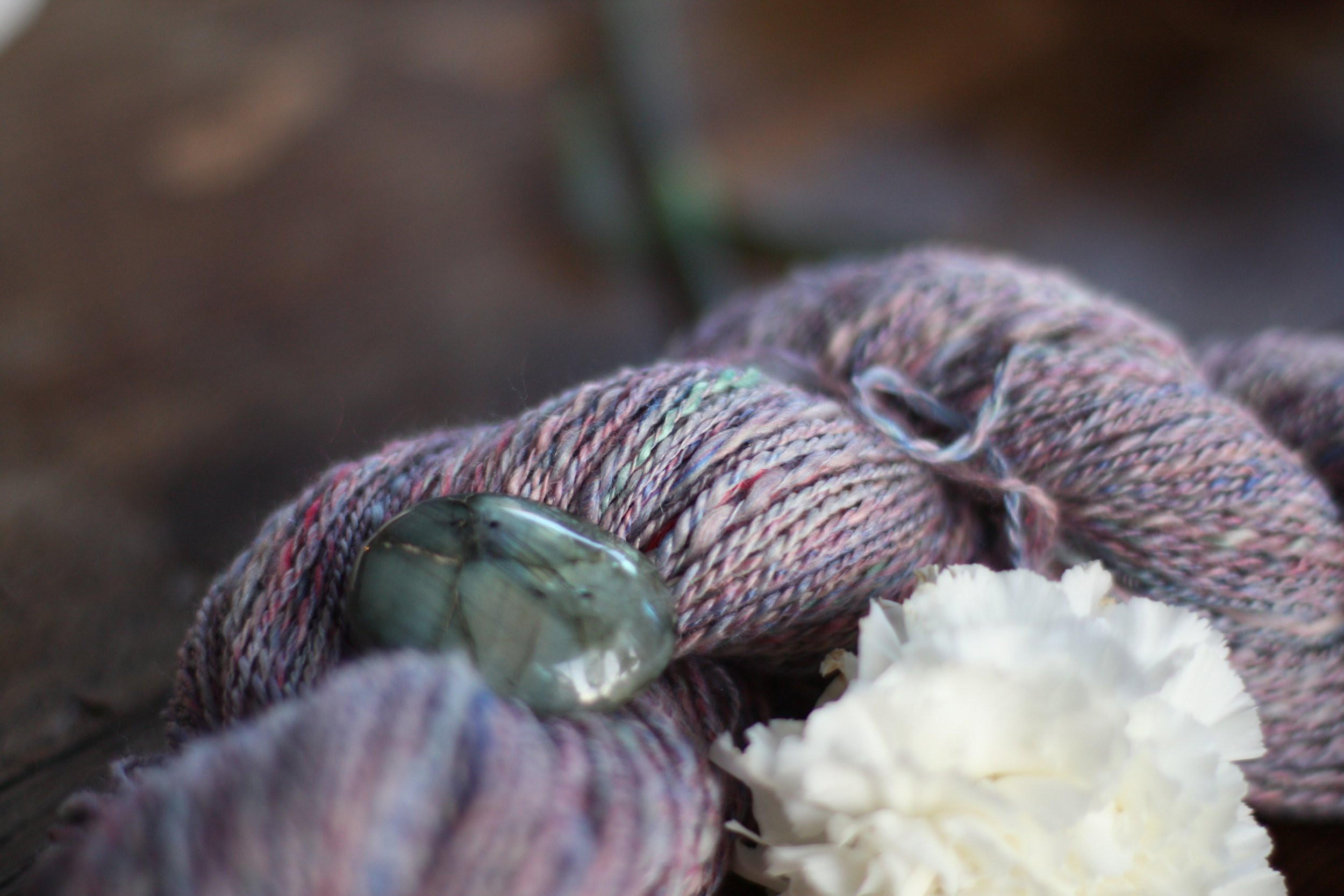 A skein of handspun yarn in pale blues and pinks with a hint of aqua poses with a labradorite stone and a white carnation | 14 Mile Farm Handweaving and Homesteading