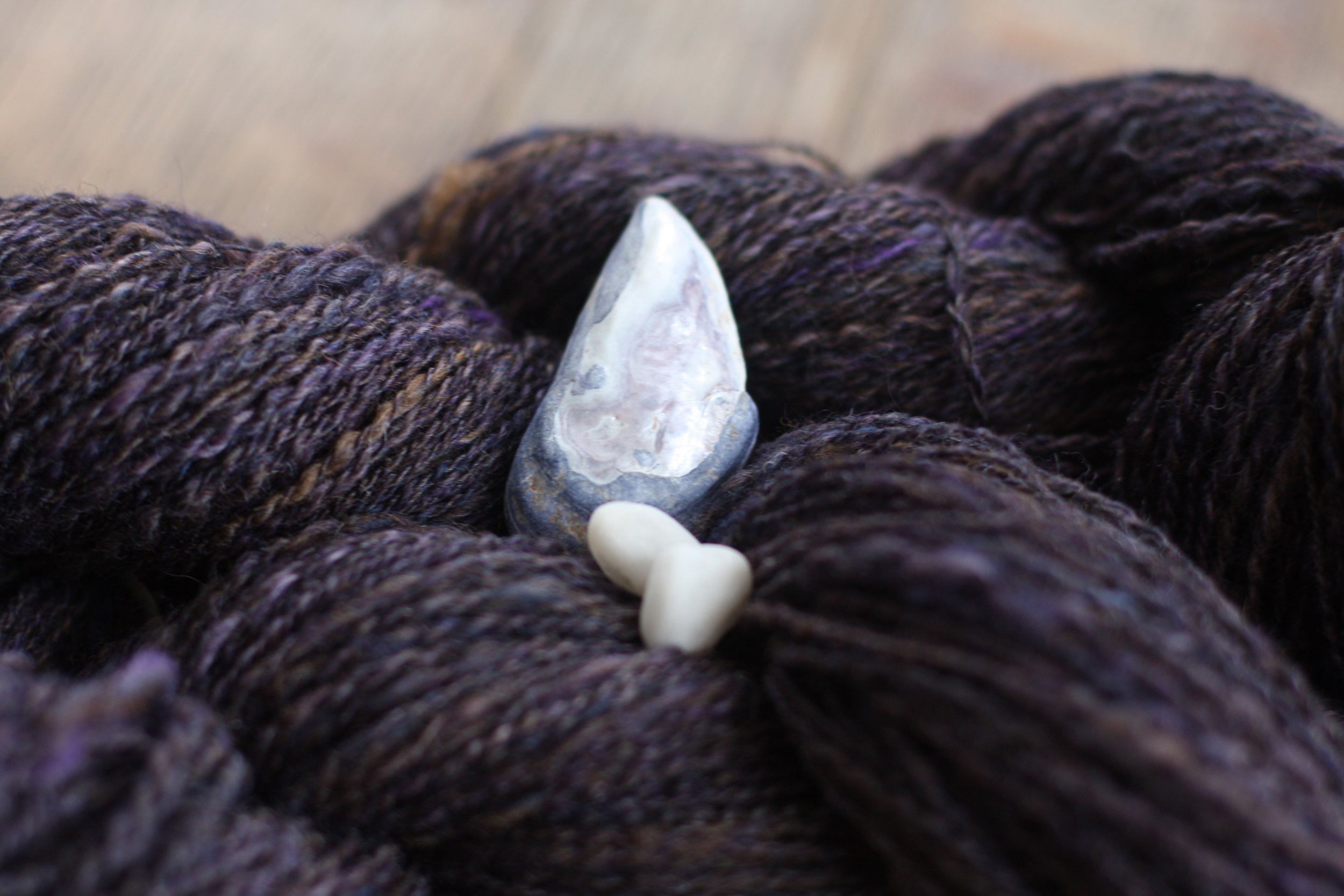 Handspun yarn featuring tones of brown and purple and blue poses with a mussel shell from the Maine coast and two quartz beach rocks | 14 Mile Farm Handweaving and Homesteading