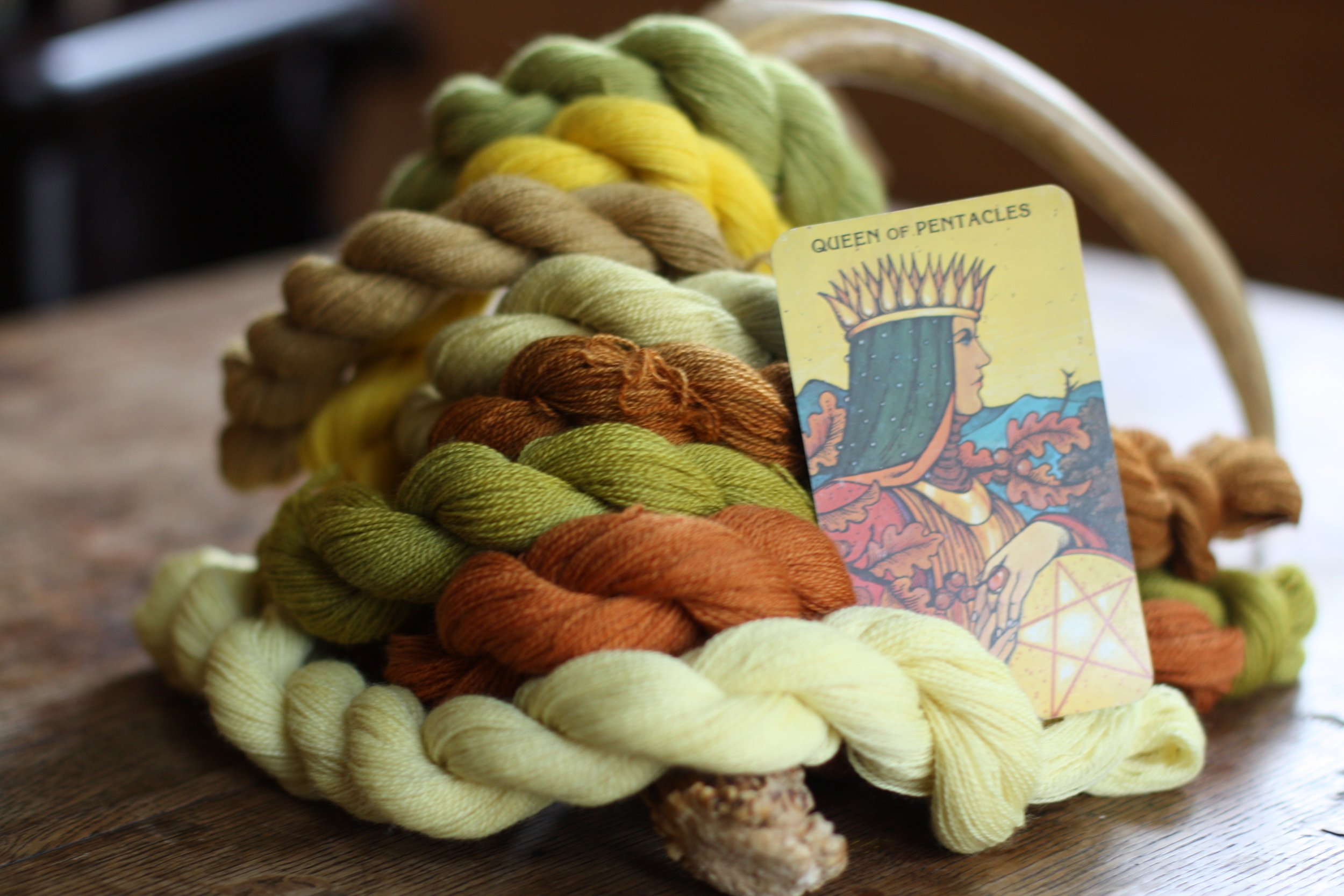 The Queen of Pentacles tarot card and skeins of wool dyed with plant dyes pose with an antler | 14 Mile Farm Handweaving