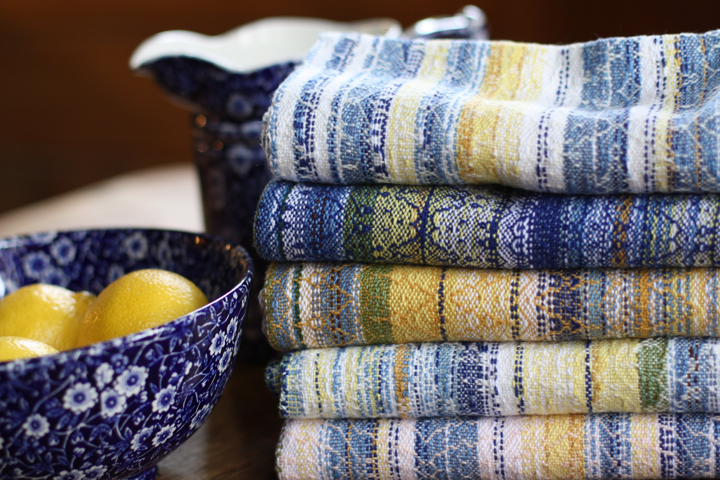 Farmhouse kitchen tableau: 5 handwoven tea towels, a pitcher, and a bowl of lemons | 14 Mile Farm Handweaving