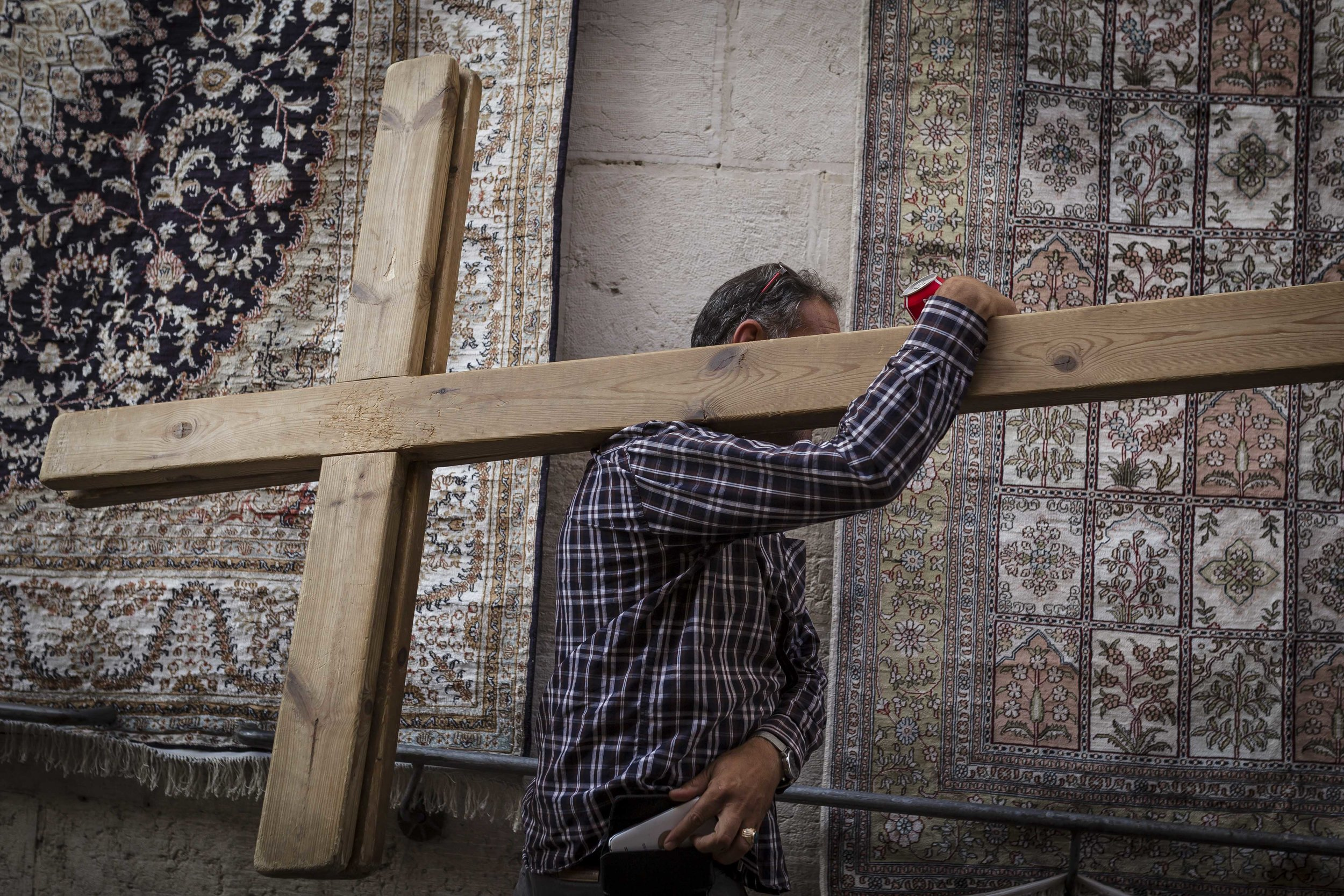 An arab men carries two crosses from the 9th station of the Via Dolorosa to the first station. Seen in Jerusalem's Old City on October 23th, 2016. The circuitous route is believed by many to follow the path that Jesus walked, carrying his cross, on the way to his crucifixion.