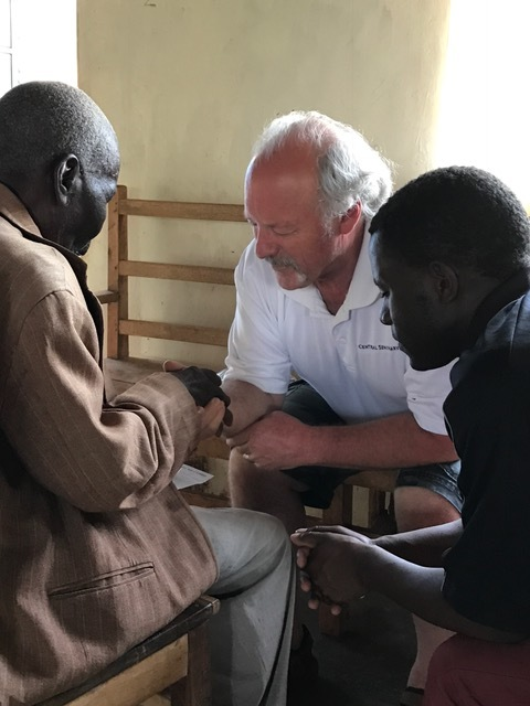 Randy praying for patients at the medical clinic.