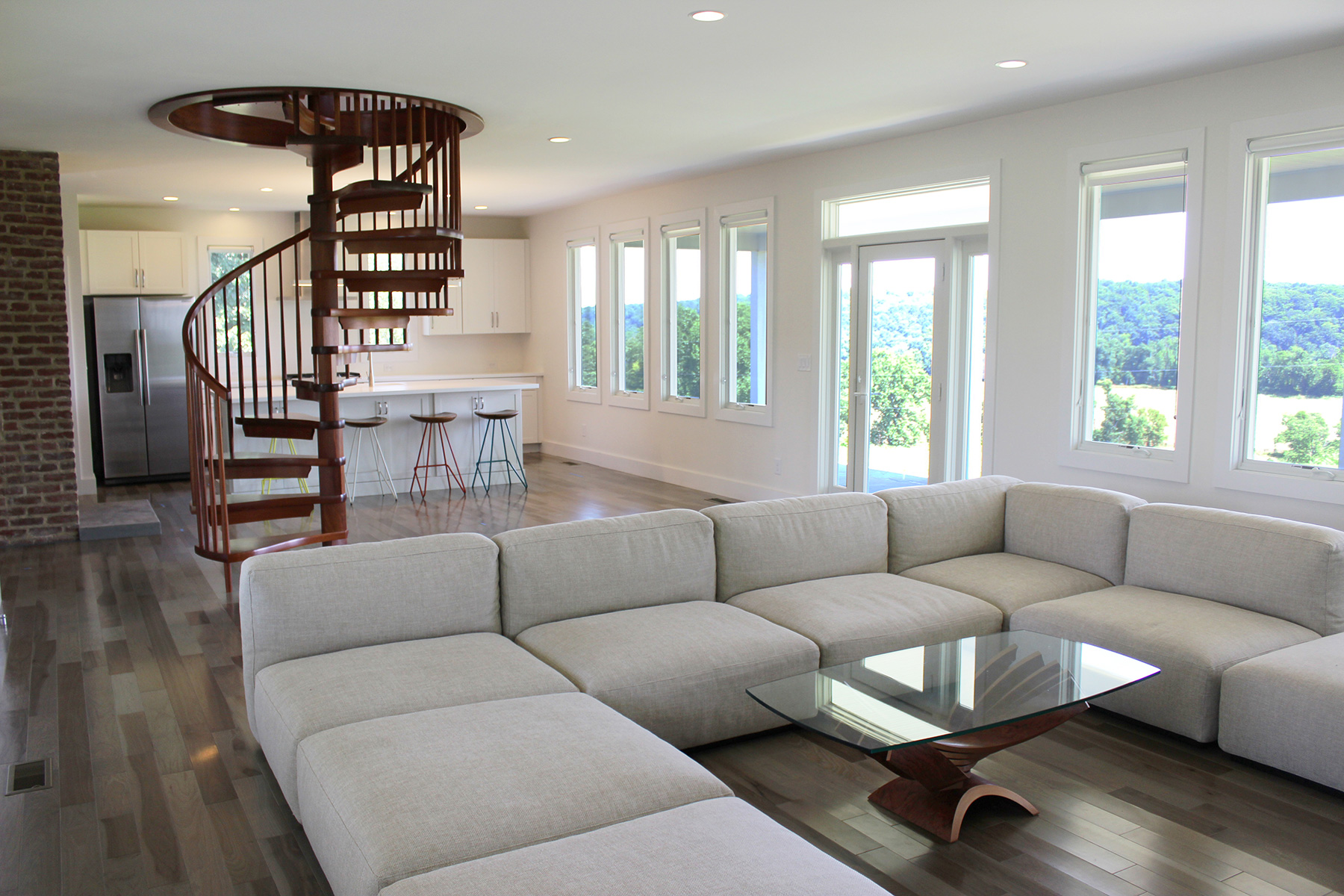 FINISHED LIVING ROOM WITH HANDMADE CUSTOM MAHOGANY SPIRAL STAIR.
