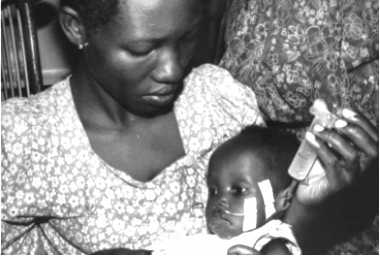 Mother feeding child at the Mwanamugimu Nutrition Rehabilitation Unit, Mulago, Uganda, c. 1965