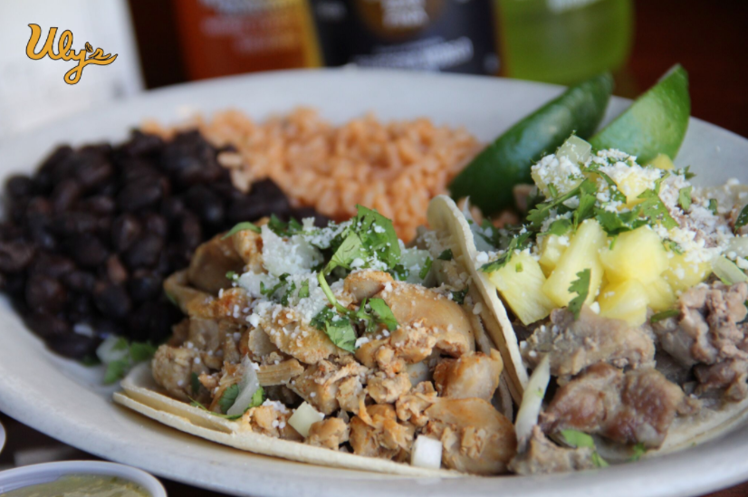 Pollo Taco and Al Pastor Taco topped with cotija cheese, served with a side of rice and black beans.
