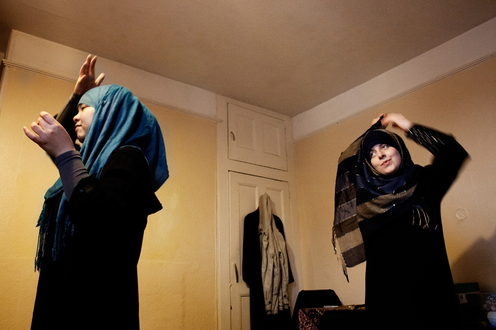 Khadija and Deryn covering their hair before leaving the house.