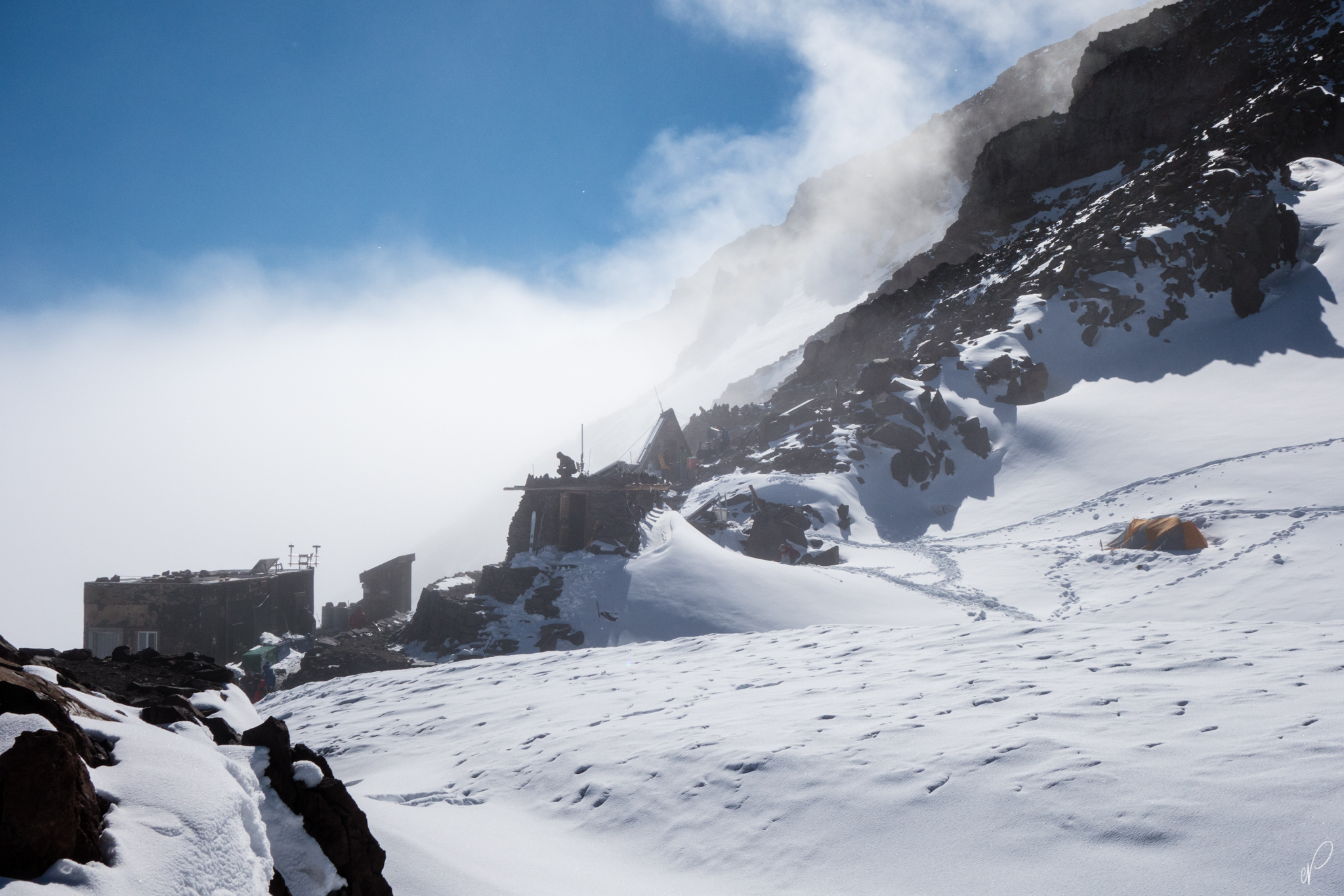Camp Muir barely over the clouds. the building on the far left is the bunkhouse for guided trips. The crouched man is over the climbing ranger hut. The pyramid structure in the middle is the hut for guides, fitted with solar panels to power the huts.