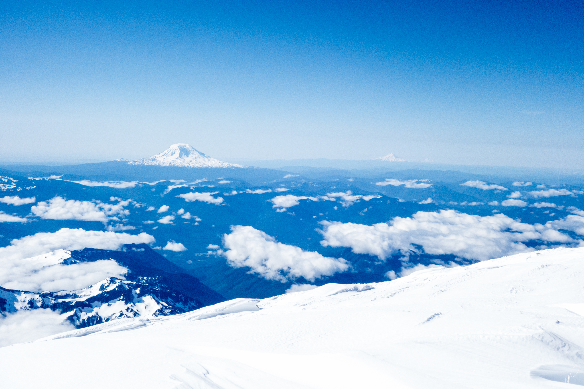 From left to right, Mount Adams, Mount Hood, with Mount Jefferson barely visible (just to the right of Hood, in the far far distance). Note the slight curvature of the planet.
