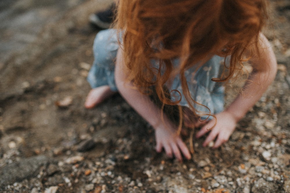 little girl playing in sand on the beach, red hair curls