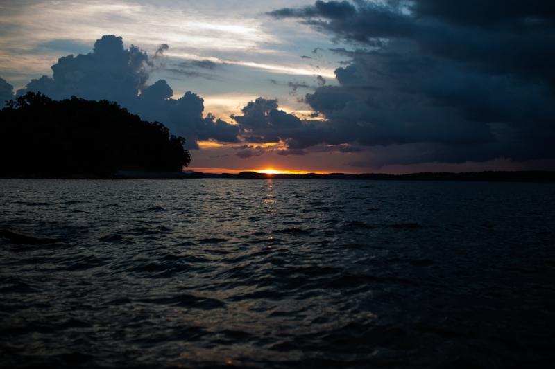 dark waters at lake lanier georgia at sunset with big clouds