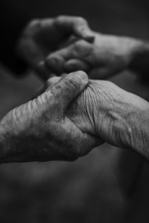 old couple holding hands close up in black and white