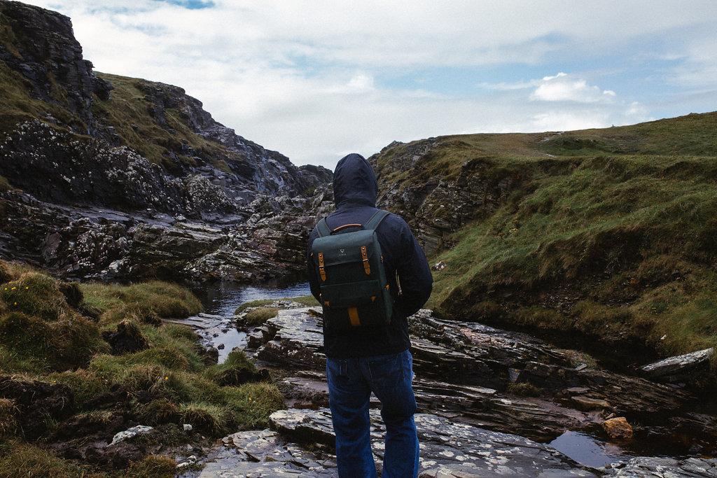 man in malin head ireland ravine wearing vinta co adventure camera bag