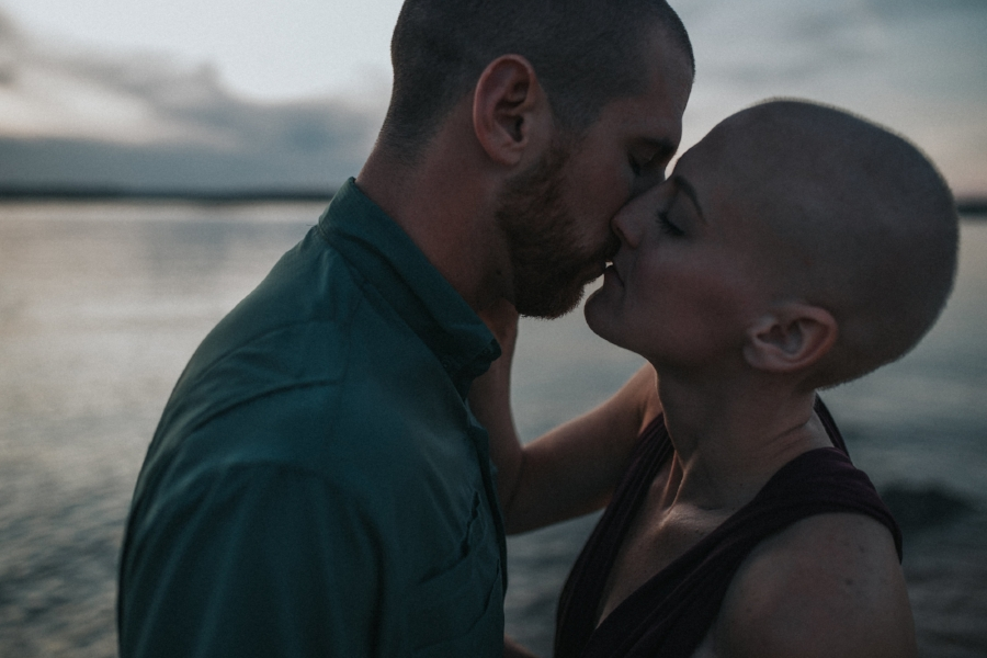 dark and moody and romantic photo of a couple about to kiss, holding each other close in front of the lake ocean after sunset
