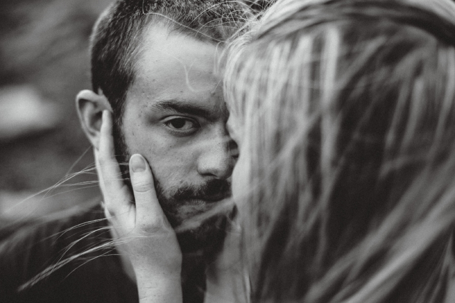 dark and moody romantic photo of man looking into camera as woman holds his face and her hair blows in the wind