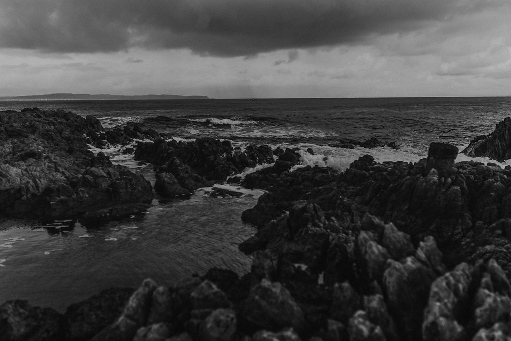 dark clouds and waves roll in over jagged rocks at rathlin island coast by ballycastle in northern ireland by meri daugherty photography