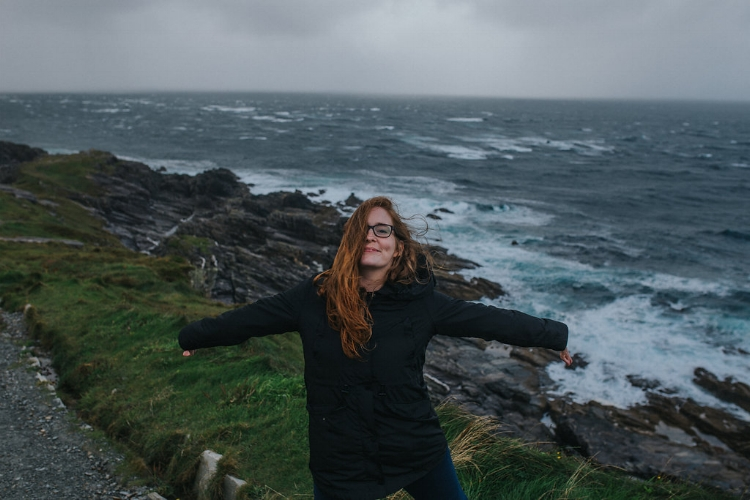 meri daugherty long redhair holding out arms in glee at malin head coast in county donegal ireland