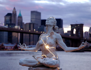 Expansion , by Paige Bradley  [image: A statue of a naked woman meditating in lotus position sits in front of a city skyline. The statue is cracked in multiple places, with light glowing from within in, shining through the cracks.]