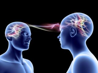 [image description: A graphic art image of two human shapes looking at each other. Inside their heads, there are blasts of color, representing neural activity. Some of those blasts of color (neural activity) are bridging the physical gap between the two people, representing mirror neurons. Thanks Psychology Today.]