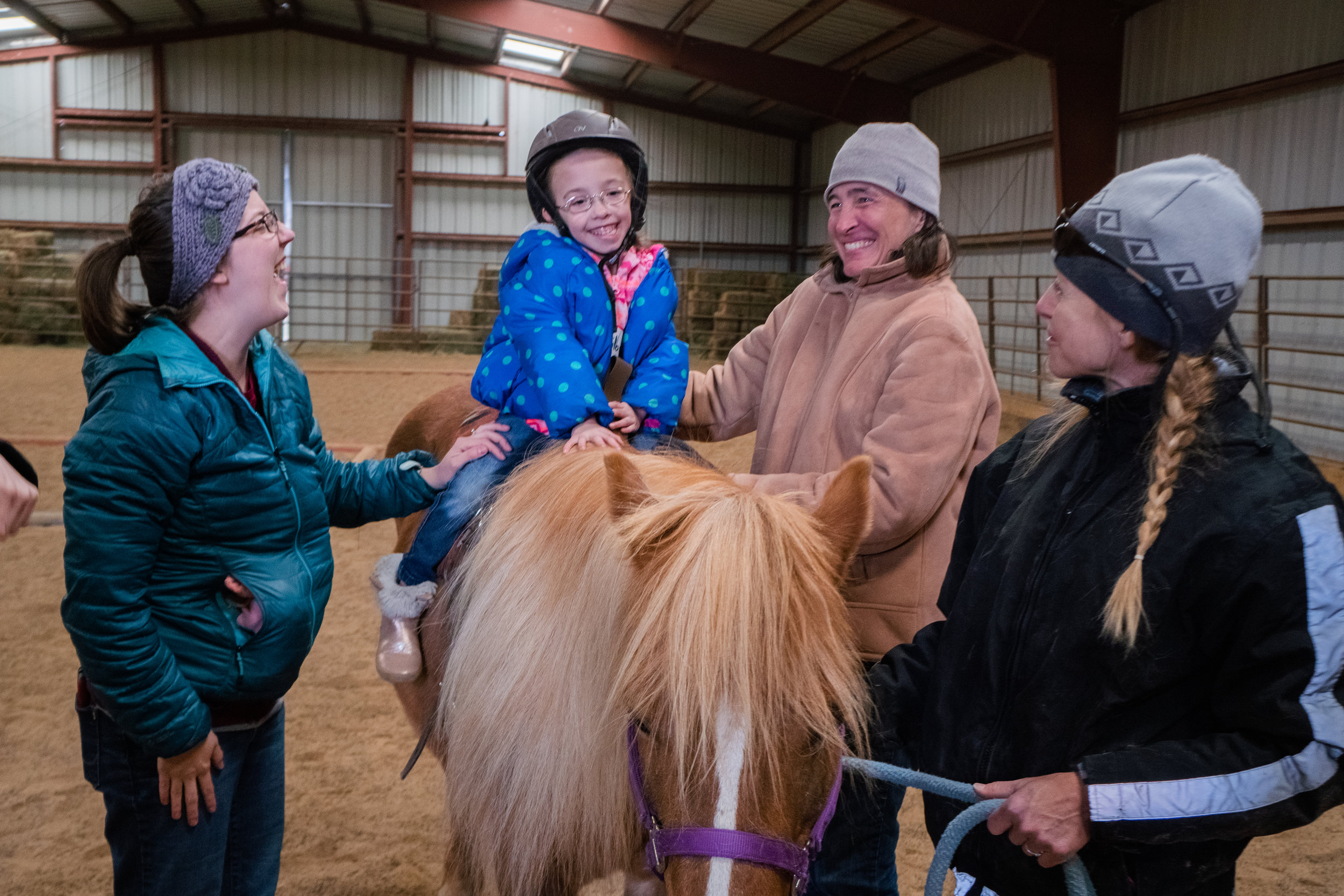 [photo taken during an Early Literacy event in collaboration with CSDB. Image of a young child riding on a horse with three adults around her. They are all in winter coats and hats, and all smiling.]