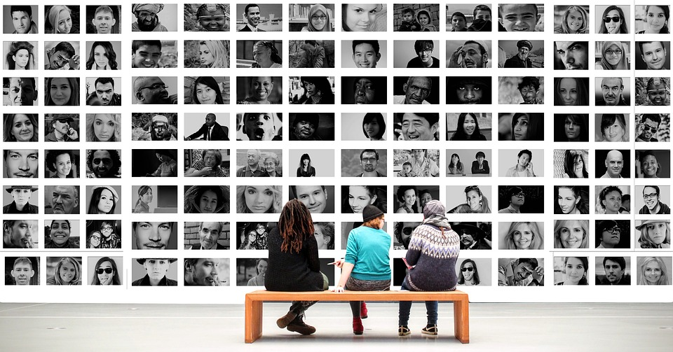 [image of three people sitting on a bench, facing away from the camera. They are looking at a wall full of portraits of many different people.]