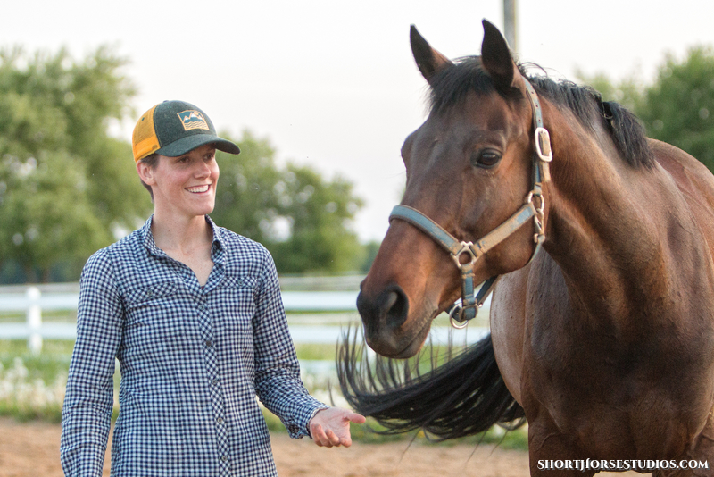 [image: photo of Jessica Dallman in a green and yellow hat, and a blue and white long-sleeved button-down shirt. Jess is gently reaching towards a bay horse, palm up, while smiling. The horse is turning towards Jess. Photo by  ShortHorse Studios .]