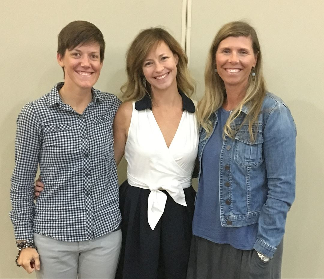 Photo: L to R, Jessica Dallman (wearing a blue and white checkered button-down shirt and grey pants), Elizabeth Seeliger (wearing a dress with a white top and black skirt), and Leigh Hardin (wearing a grey skirt, blue blouse, and jean jacket).