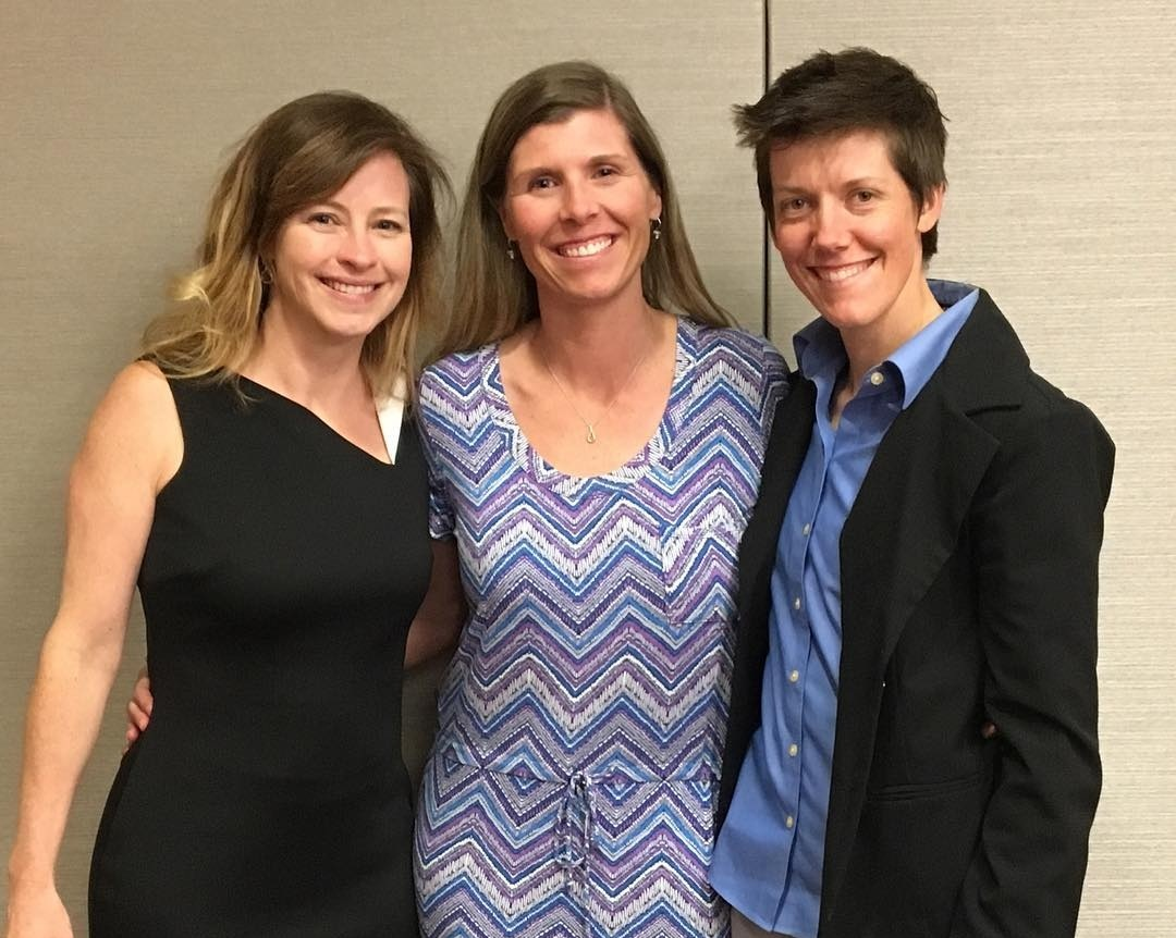 Photo: L to R, Elizabeth Seeliger (wearing a black dress), Leigh Hardin (wearing a blue, white, and purple zig-zag striped dress), Jess Dallman (wearing a blue button-down shirt and black suit jacket).