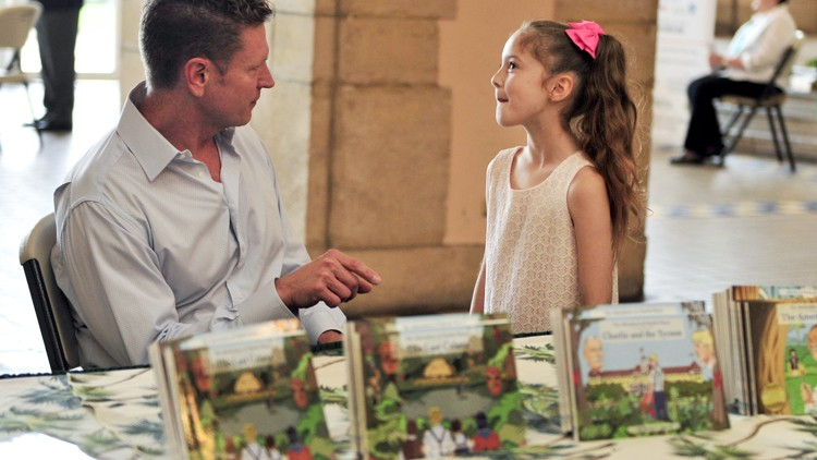 "Harvey Oyer chats with Hailey West, 9, of Port St. Lucie during Oyer's ""Charlie and the Tycoon"" book launch and signing Saturday at the Flagler Museum. Activities included crafts, a sea-grape jelly cooking demonstration and Gilded Age games. Robert Avossa and Ric and Dorothy Bradshaw also read chapters of the book to visitors.  PHOTO: MEGHAN MCCARTHY"