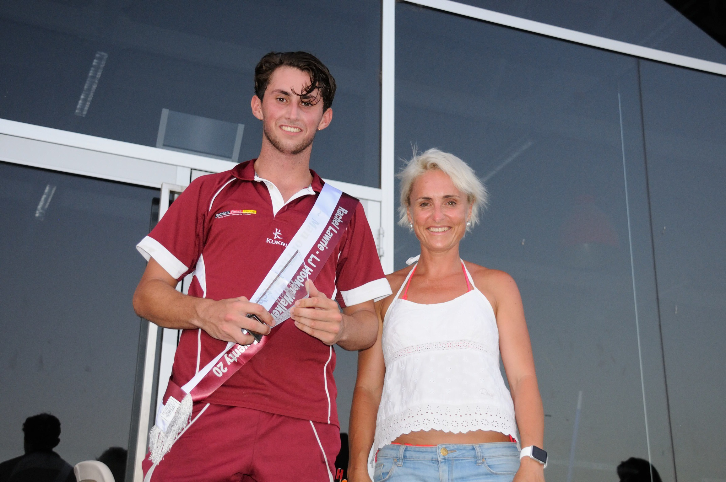 Fynn Hudson-Prentice receiving his Man of the Match trophy from one sun loving real estate sales person/organiser and maybe slightly worn out.