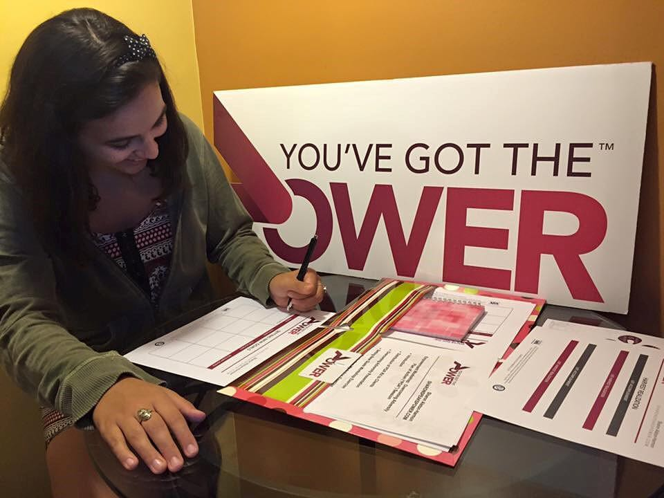 - Power Workshop Attendee Using Her Plan of Action Empowerment Kit to Set and Achieve New Goals