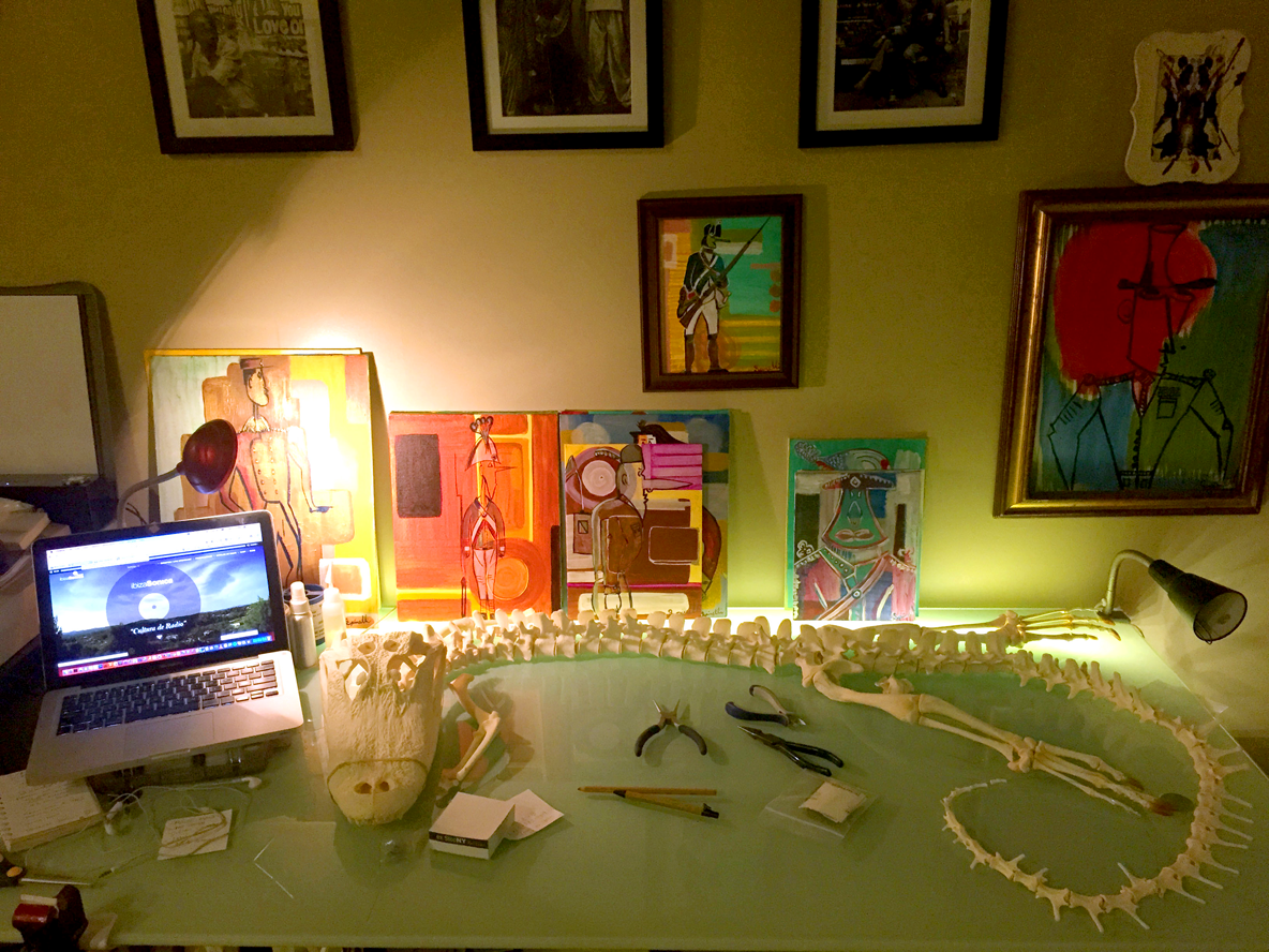 "My desk at the moment. I'm articulating a real 8 foot long alligator skeleton for my next sculpture project. Of course overlooked by some of my trustful and loyal ""Love Lieutenants"". Just wait and see what the art world has in for me, or what I have in store for the art world."