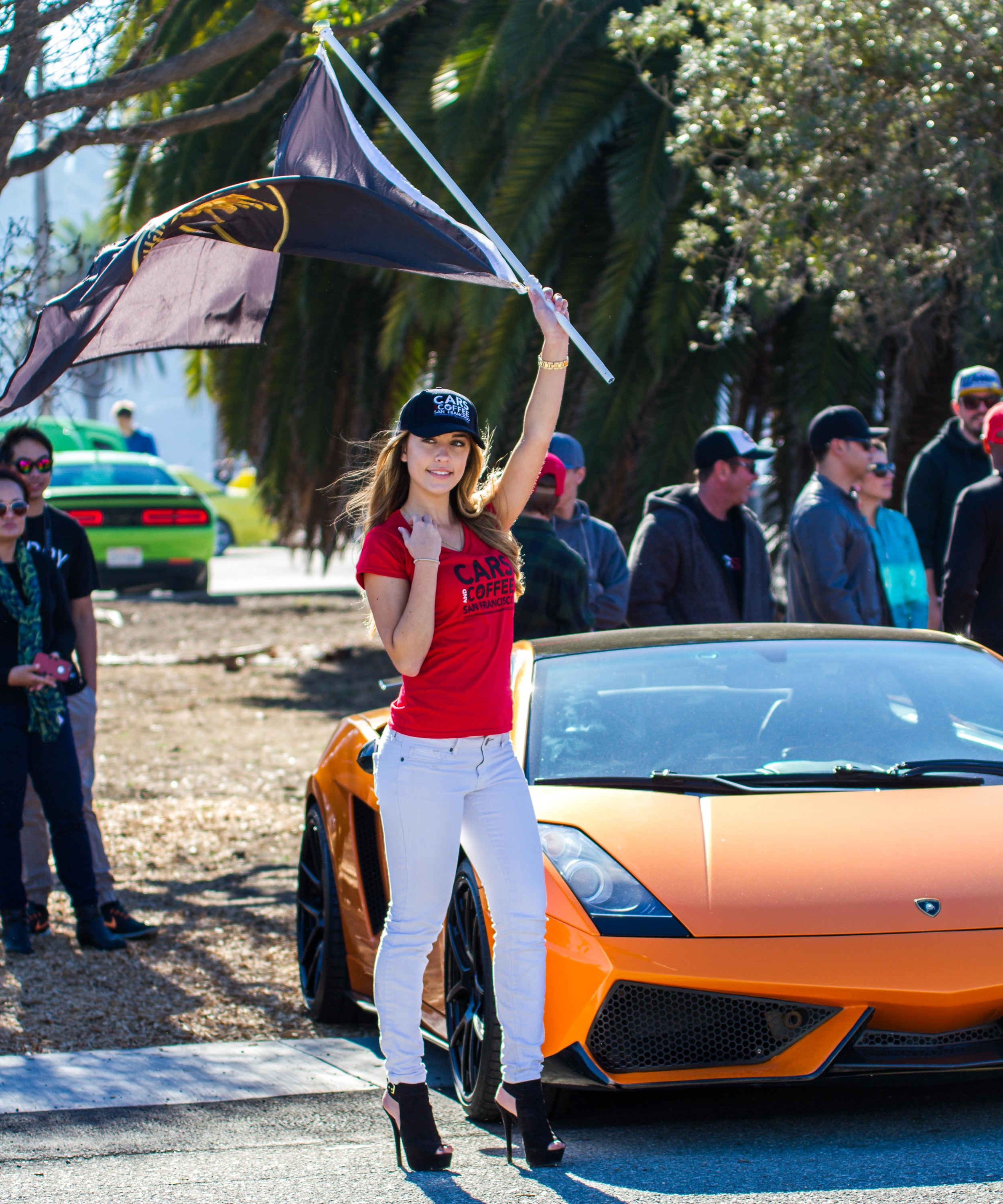 One of the Cars and Coffee San Francisco Girls holding a Lamborghini flag in front of a Lamborghini Gallardo.