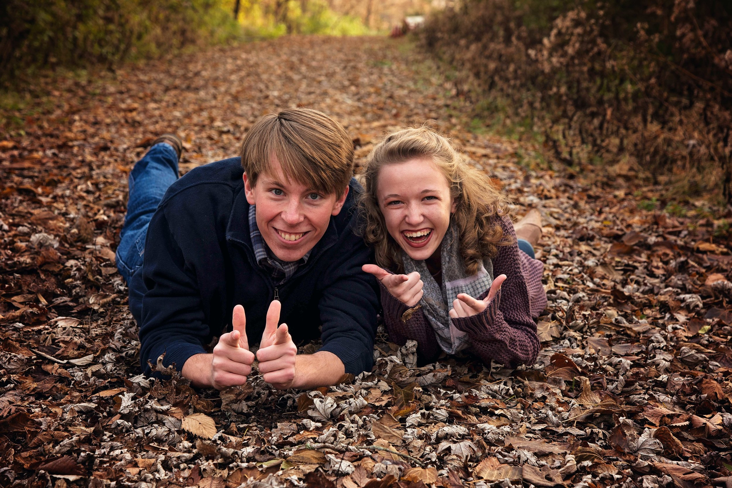 High School Guy and Girl laying in leaves on trail Senior Portraits Cincinnati Remember When Portraits