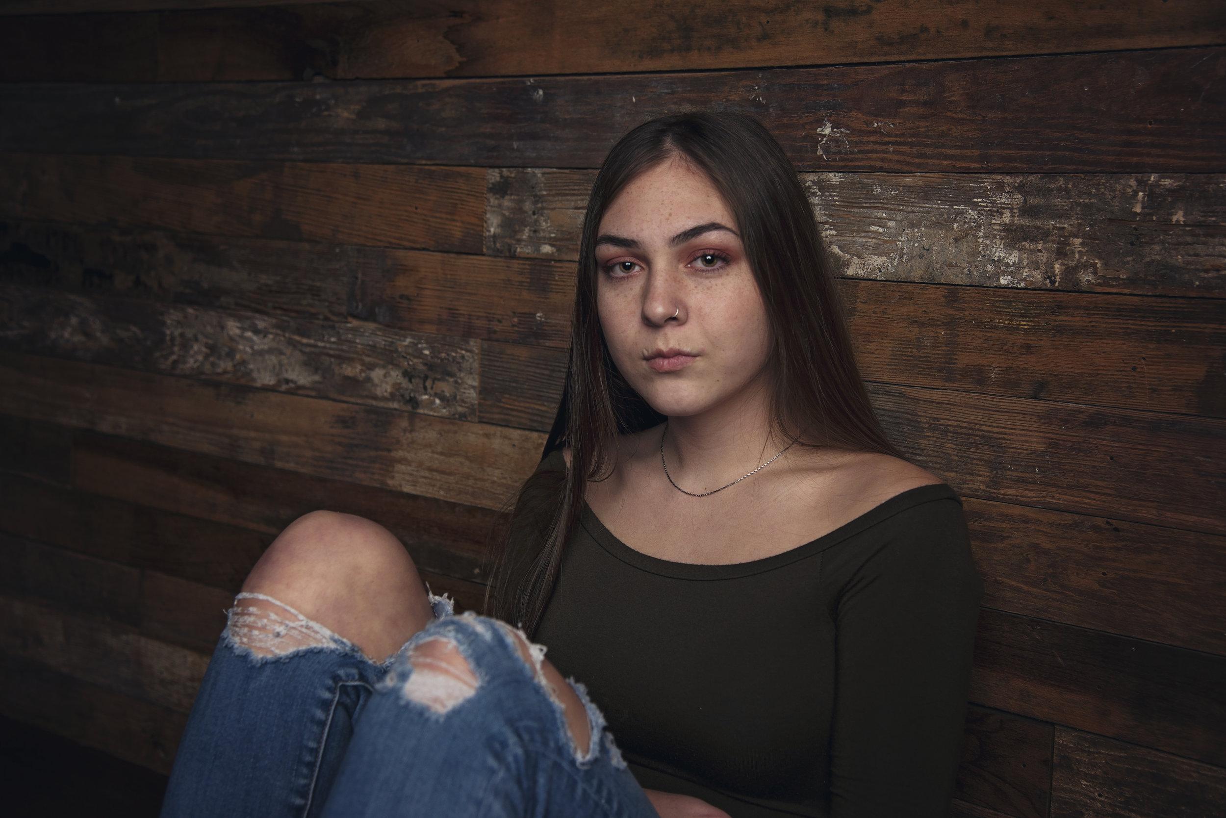 High School Senior Girl sitting knees up against a barn wood wall Remember When Portraits Cincinnati Senior Photographer