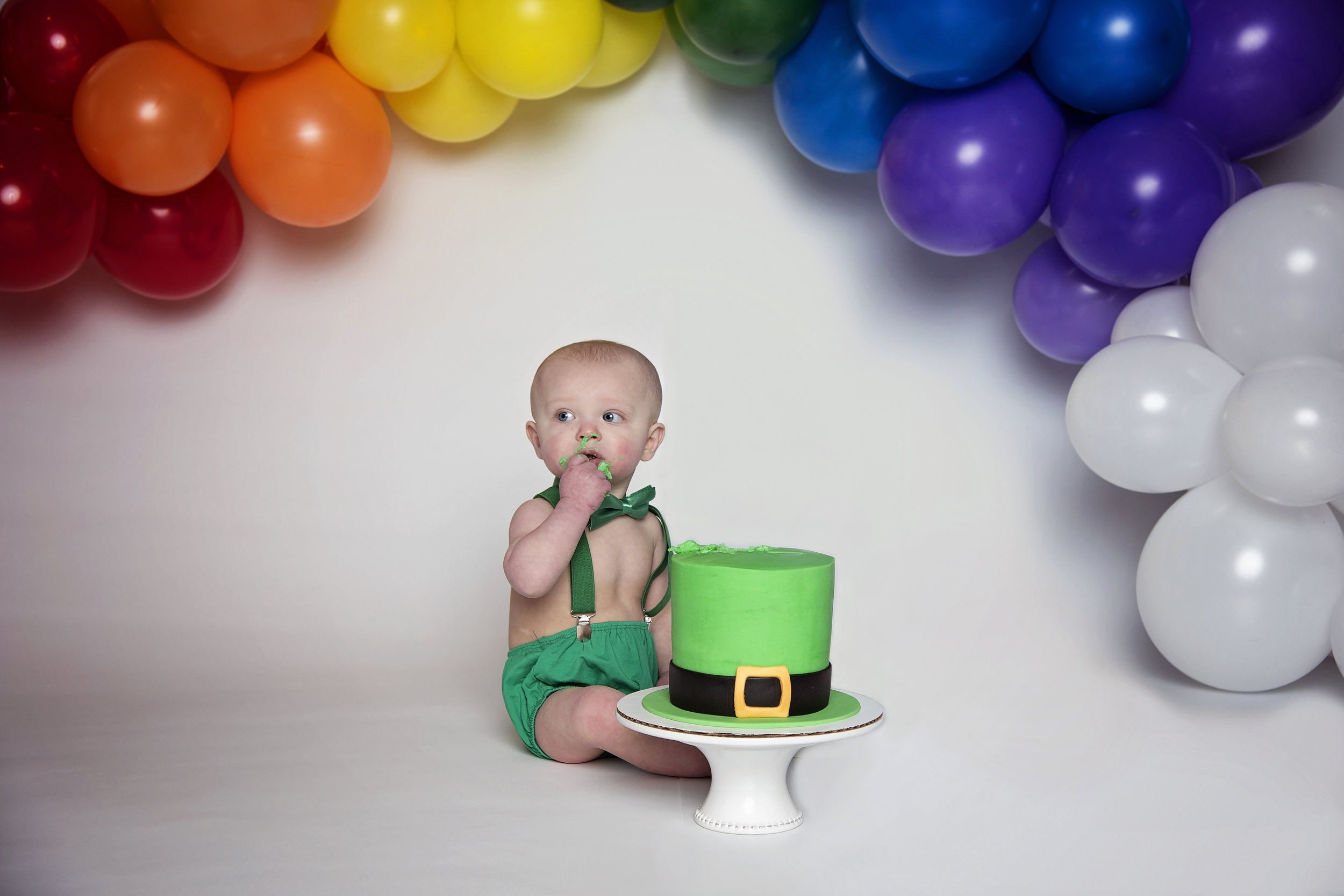 First Birthday Cake Smash Cincinnati Ohio St Patrick's Day Theme Little Boy Eating Cake in Green Outfit Remember When Portraits