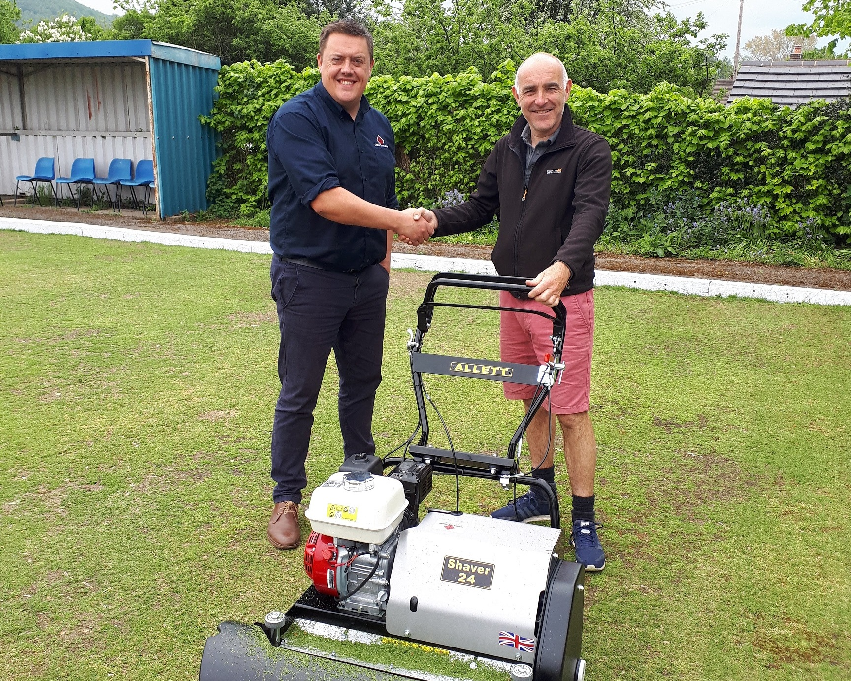 Head Greensman Barry Ellams (R) receiving the mower from Greg Cain from Cheshire Turf Machiner