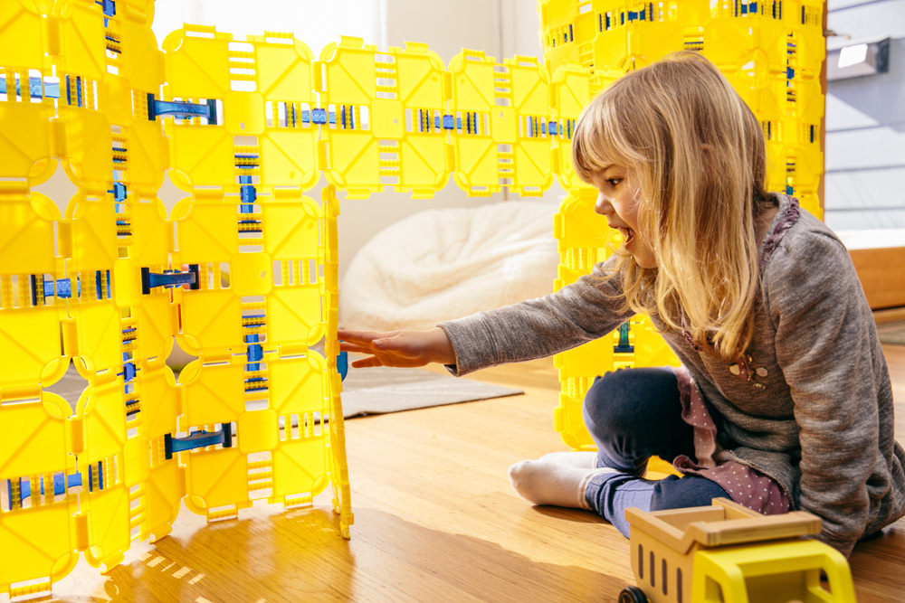 A young girl plays with Fort Boards, a STEM toy and fort building kit