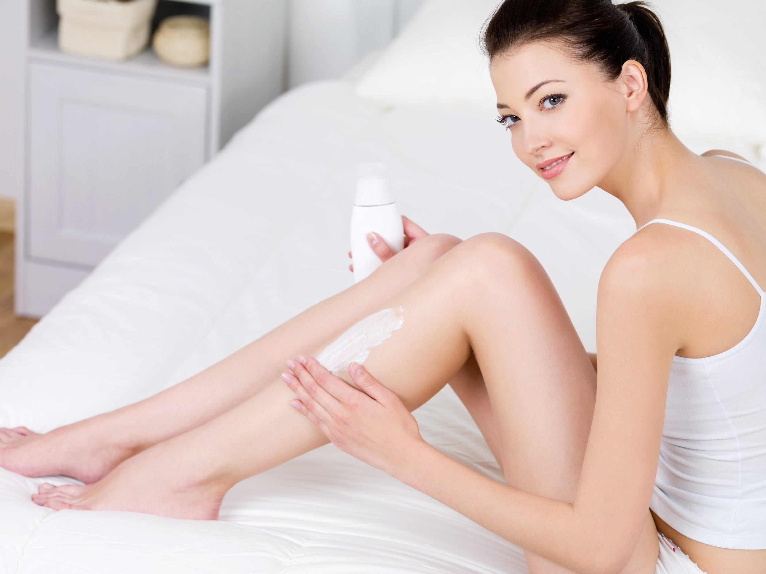 Woman applying body lotion on her legs