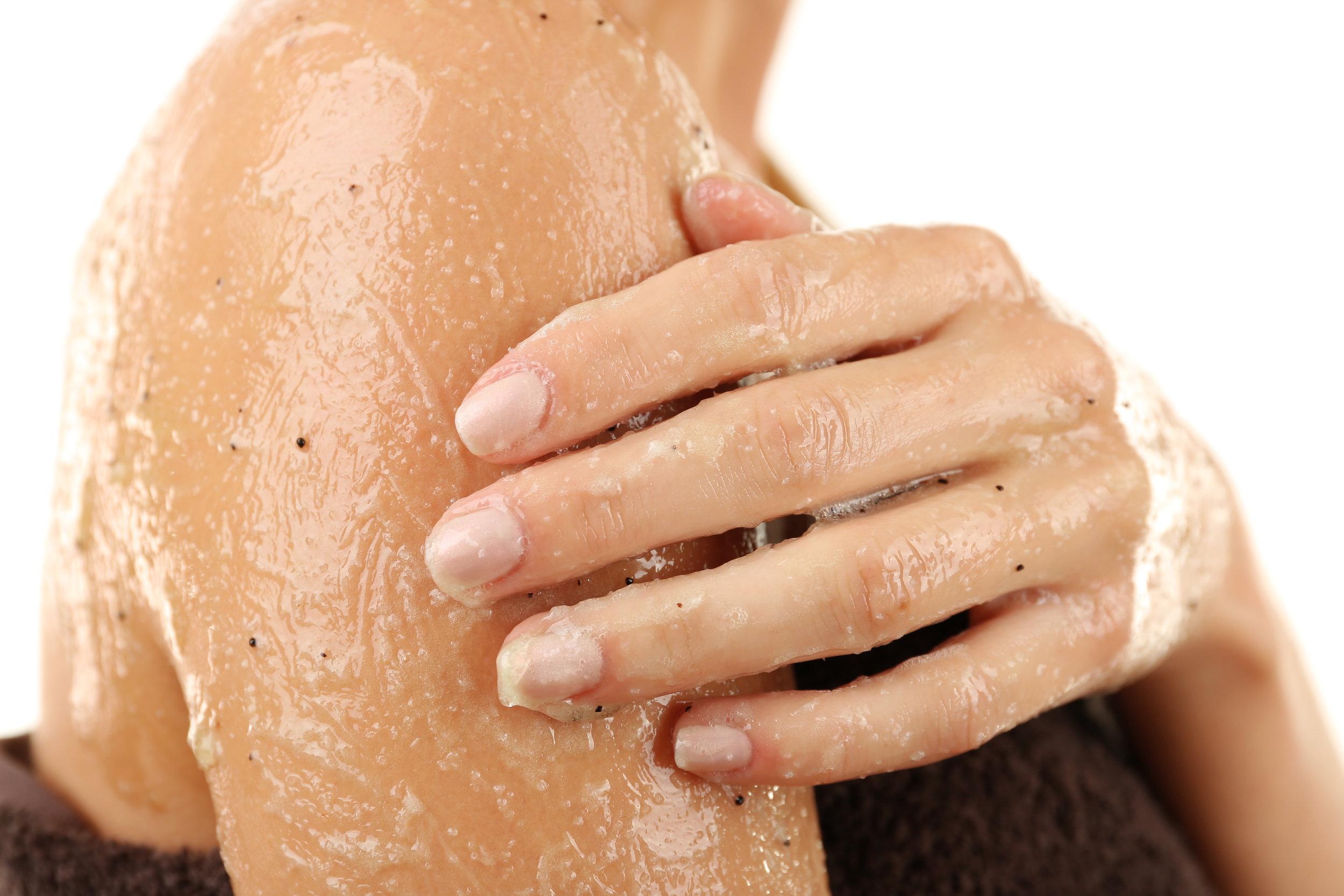 Woman using body scrub isolated on white