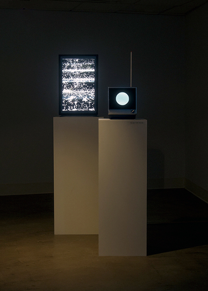 Installation view of (left):   Day Becomes Night  , 2014; Video (color, silent, 00:23 looped); media player; vertical monitor on pedestal and (right):   Planet of the Blind  , 2015; modified TV, aluminum, vinyl, paint