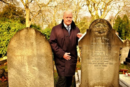 City of London Cemetery and Crematorium Superintendent Gary Burks stands between two graves—one original, one reused.