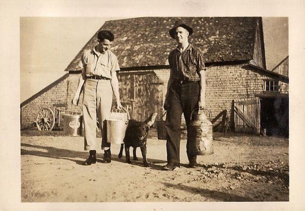 Dad (in hat) with a pal, looking entirely too happy and handsome to be doing farm chores.