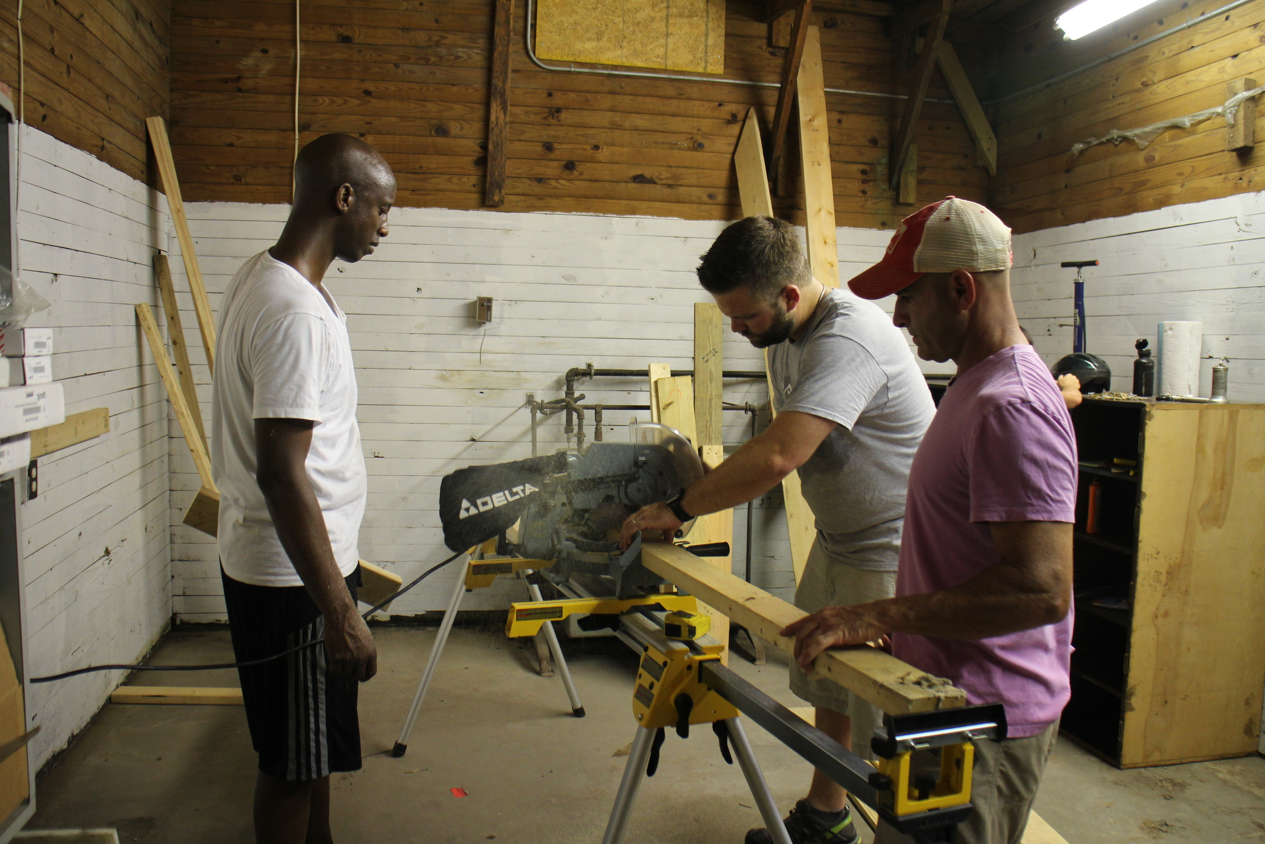 This is Thomas Livoti, Amos Disasa, and Brad Allen constructing the work bench. Amos is cleverly standing behind the chop saw so the saw dust blows all over him. Then, everyone will think he worked hard. Thomas looks like he is worried about the future of Brad's left hand.