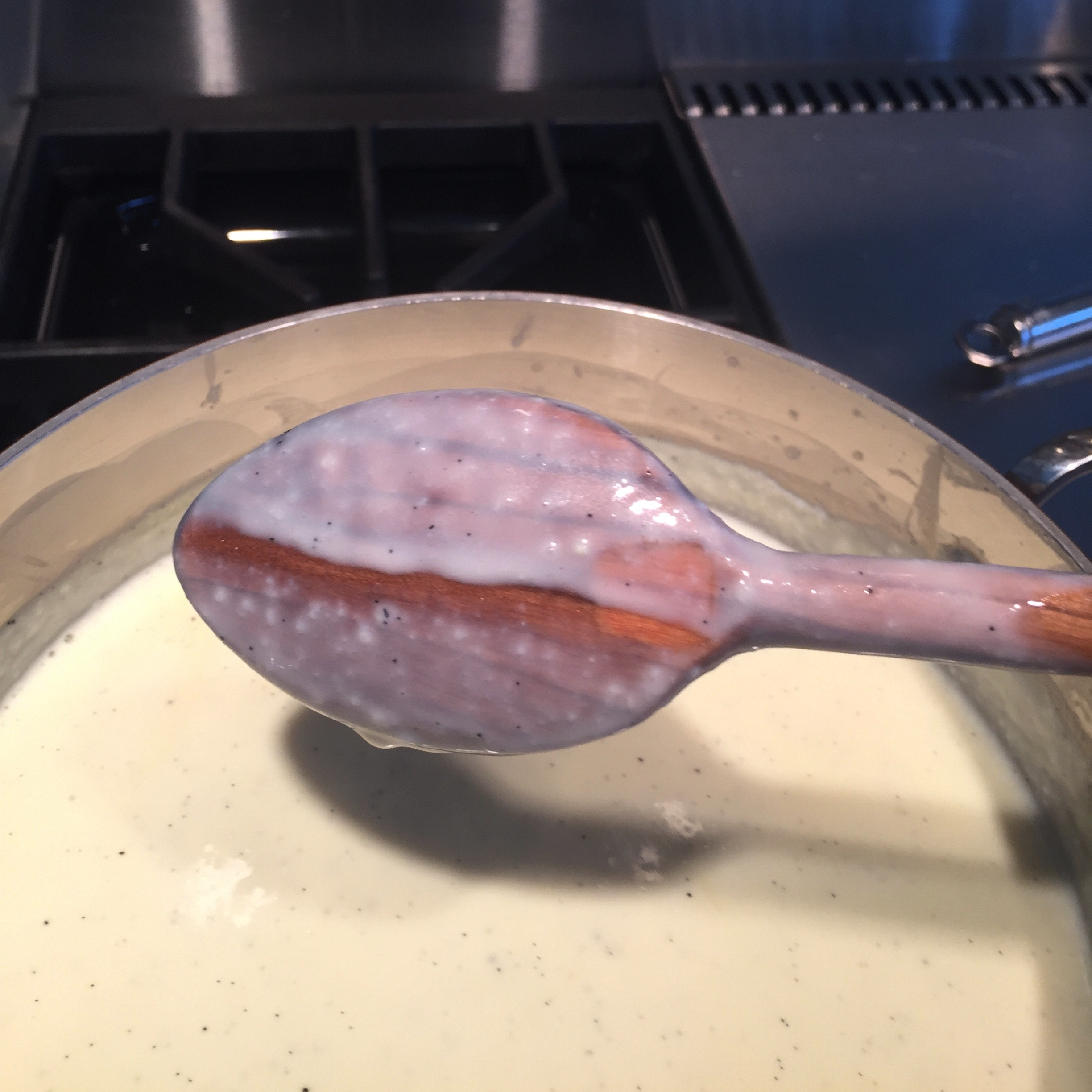 This custard is finished cooking. When you draw a line with your finger through the custard clinging to the back of the spoon it does not fill in.