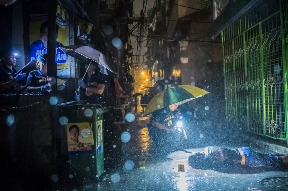 In a downpour, SOCO (scene of the crime operatives) for the Manila police investigated in an alley where a man named Romeo Joel Torres Fontanilla, 37, had been killed by two unidentified gunmen riding motorcycles in the early morning of Oct. 11, 2016. (Award of excellence, General News.)  Daniel Berehulak for The New York Times