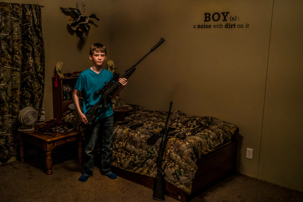 Drew Moore, 11, posing with his air gun collection in his bedroom, where the definition of a boy is stenciled on the wall. In his Arkansas community, hunting and manhood are entwined.   Pete Muller/PRIME for National Geographic